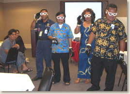 EAD & Associates, LLC carried out an exercise with emergency managers in American Samoa. In this photo, four managers wear special glasses that simulate different visual disabilities to experience what it is like to navigate a reception center or follow recovery instructions with a disability.