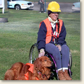 Woman in a wheelchair with service dog dressed in CERT team uniform