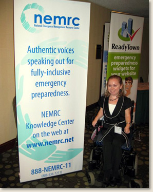 Kelly Rouba, of EAD, with the National Emergency Management Resource banner at the enABLED in Emergencies conference in Philadelphia, PA